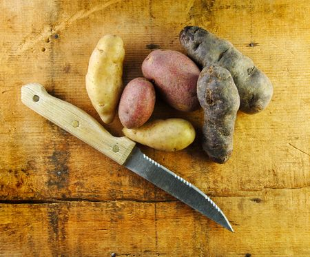 fingerling: Fingerling potatoes in three colors on a rustic table with a knife.