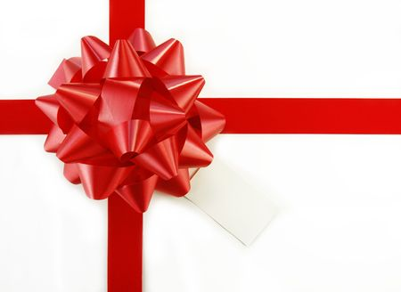 Red bow and ribbon on white gift box with tag. Stock Photo