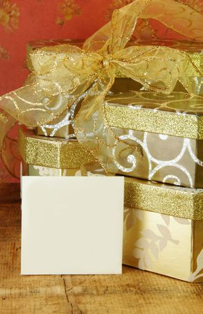 Gift boxes stacked with gold ribbon and gift card blank for your text. photo