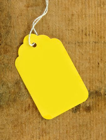 Yellow tag on wooden surface with copy space for your text.