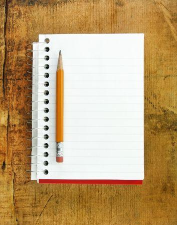 lapiz y papel: L�piz sobre la almohadilla peque�a de papel con l�neas en blanco para el texto.