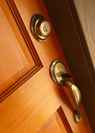 deadbolt: Brass door handle and deadbolt on wooden door Stock Photo