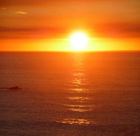 A dramatic blazing orange sunset over the pacific ocean photo