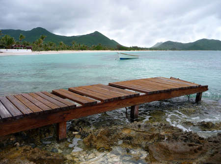 A weathered wooden pier juts into the clear water of a caribbean island photo