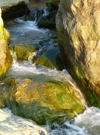 Waterfall through mossy rocks along the coast photo
