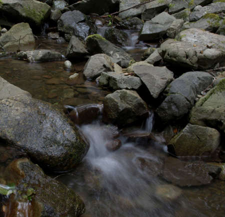 Waterfall and stream in the forest, cascading through mossy rocks photo