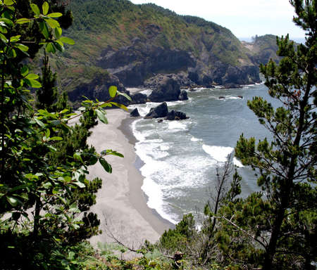 Rock outcroppings and a gentle surf on the beach in Oregon photo