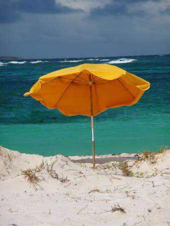 Yellow beach umbrella in the sand Reklamní fotografie