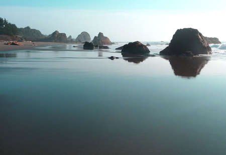 turqoise: Sky reflects a turqoise hue on the sand of a rocky beach in Oregon Stock Photo