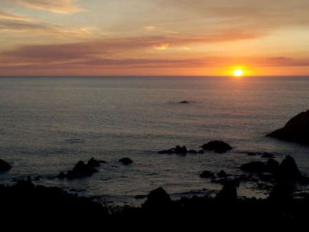 The sun appears as a blazing ball of fire as it sets on the ocean horizon photo