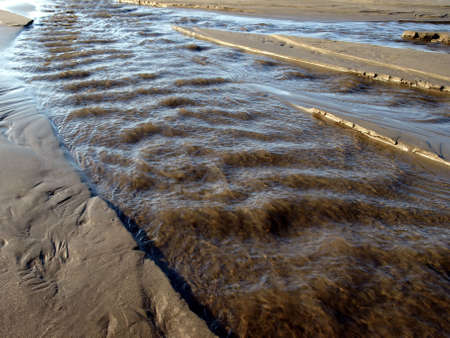 A river swells with water and rushes along a sandy beach