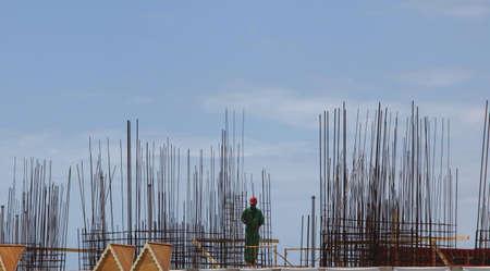 View of construction worker with hardhat on jobsite surrounded by rebar