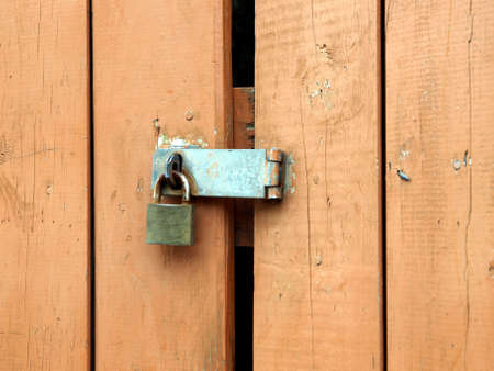 Rusty padlock and hasp on weathered painted wooden door