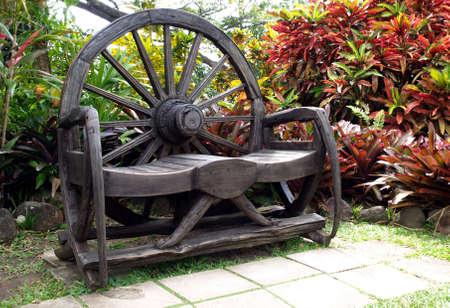 Een uitnodigende rustieke houten bank in een tuin  Stockfoto