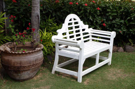 An inviting white painted wooden bench in an outdoor garden Reklamní fotografie