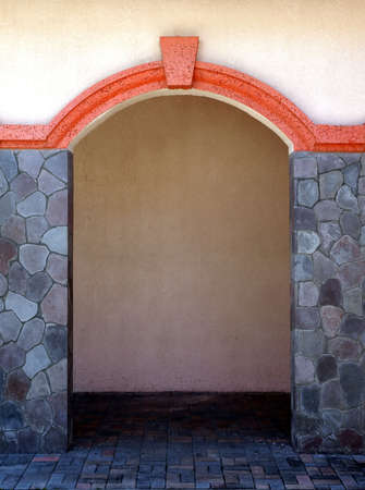 Stone pillars and colorful archway through a stucco building Reklamní fotografie