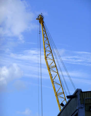 A large construction crane framed by a bright blue cloudy sky