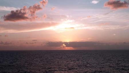Sunset colors the sky and ocean on a cloudy horizon Reklamní fotografie