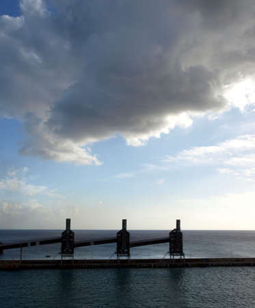 Sun sets through a dark cloudy sky and silhouettes of silos on Barbados dock