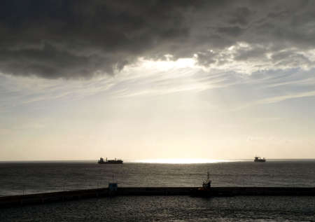 brooding: A grey and brooding sky shines sunlight on the ocean and passing freighters Stock Photo