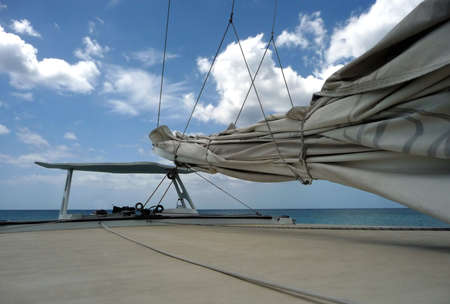 Secured mainsail and view over deck of sailboat to a bright blue cloudy sky