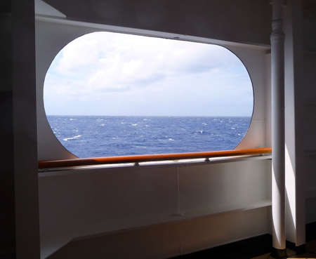 A large open window provides a view to the sea and sky