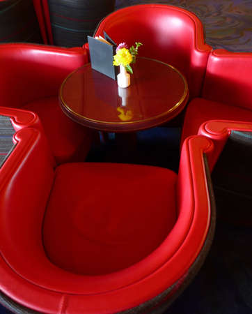 Contemporary red leather chairs around small round table