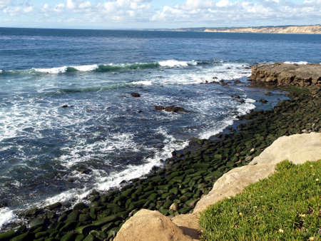 View of pacific coast with mossy rocks, gentle waves and cloudy sky