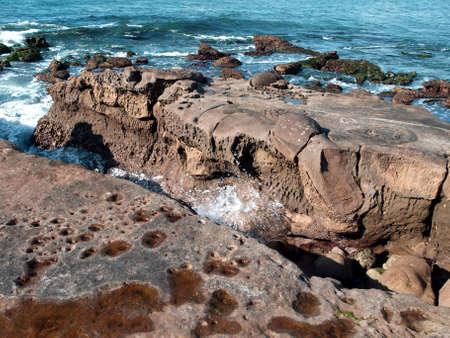 Waves and surf splash through large costal coral formations Reklamní fotografie