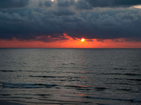Horizontal image of moody Pacific coast sunset and gentle surf