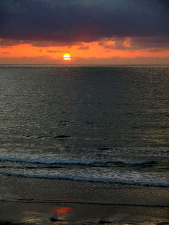 Vertical image of moody Pacific coast sunset and gentle surf