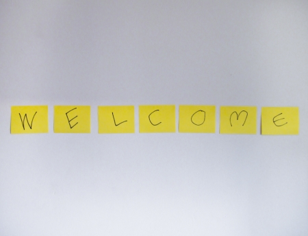 charactor: welcome word on yellow post it at white concrete wall backgrounds