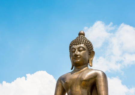 golden top half Buddha statue of thailand on blue sky photo