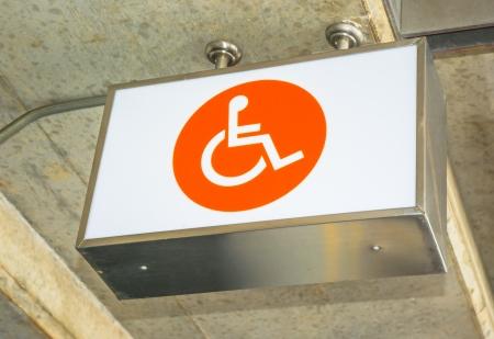 enabling: label orange sign  lightbox of cripple on concrete ceiling