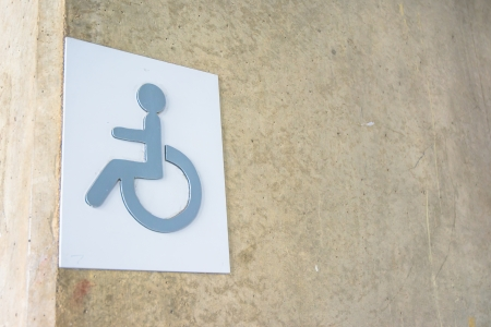 enabling: label sign metal of cripple on concrete wall