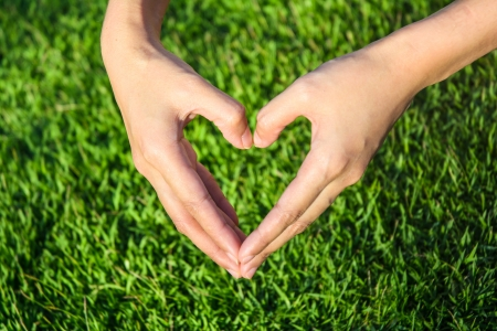 young girl hand make heart by hand on grass background photo