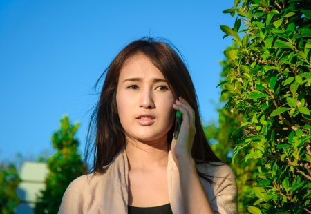 asia young girl hold mobilephone and talk on natural and blue sky background photo