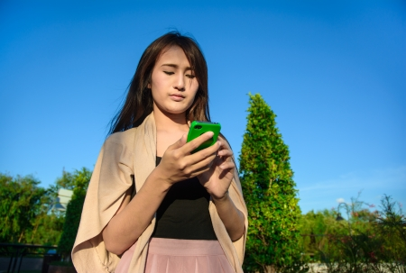 asia young girl look into mobilephone on natural and blue sky background photo