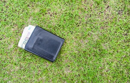 single black wallet and thailand maoney on green grass background photo