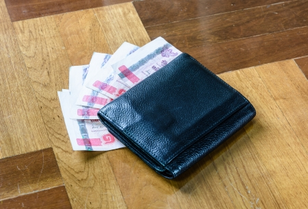 paquet: top view single black wallet with thailand money on brown paquet floor backhrounds