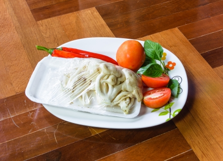 paquet: lot of white mushroom and tomato with pepper on dish for cook on brown paquet floor Stock Photo