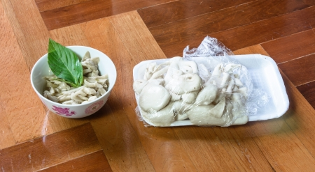 paquet: many white small mushroom in palstic package and single bowl on brown paquet floor ground Stock Photo