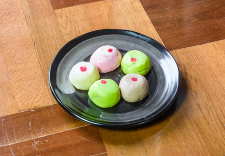 paquet: lot of color mochi cakes on single black dish on brown wood paquet floor ground