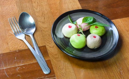 paquet: color mochi cakes on single black dish with spoon at brown wood paquet floor ground Stock Photo