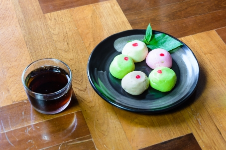 paquet: mochi cakes on black dish with black tea in glass on brown wood paquet floor ground
