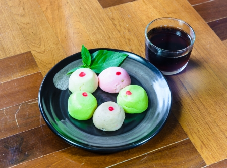 paquet: color mochi cakes on black dish with black tea in glass on brown wood paquet floor ground