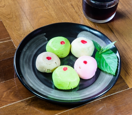 paquet: close up mochi cakes on black dish on brown wood paquet floor ground