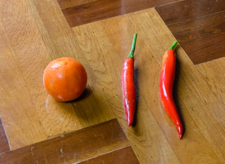 paquet: single tomato and two pepper vegetable  on brown wood paquet floor ground