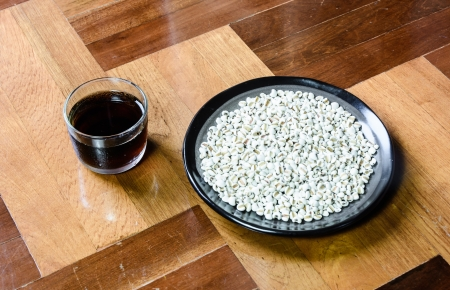 paquet: close up lot of white asia millet on dish with black tea at wood paquet floor ground