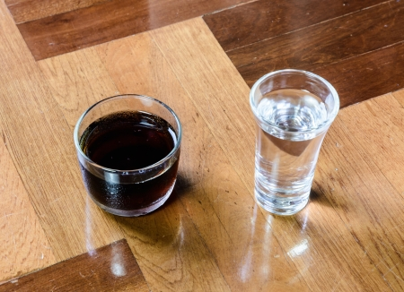paquet: black tea and clear water in small glass at brown wood paquet floor ground